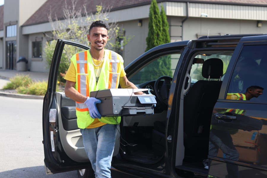 Jagit Singh of ATL Adventure Services carries an old printer. (Dariya Baiguzhiyeva/Niagara Now)