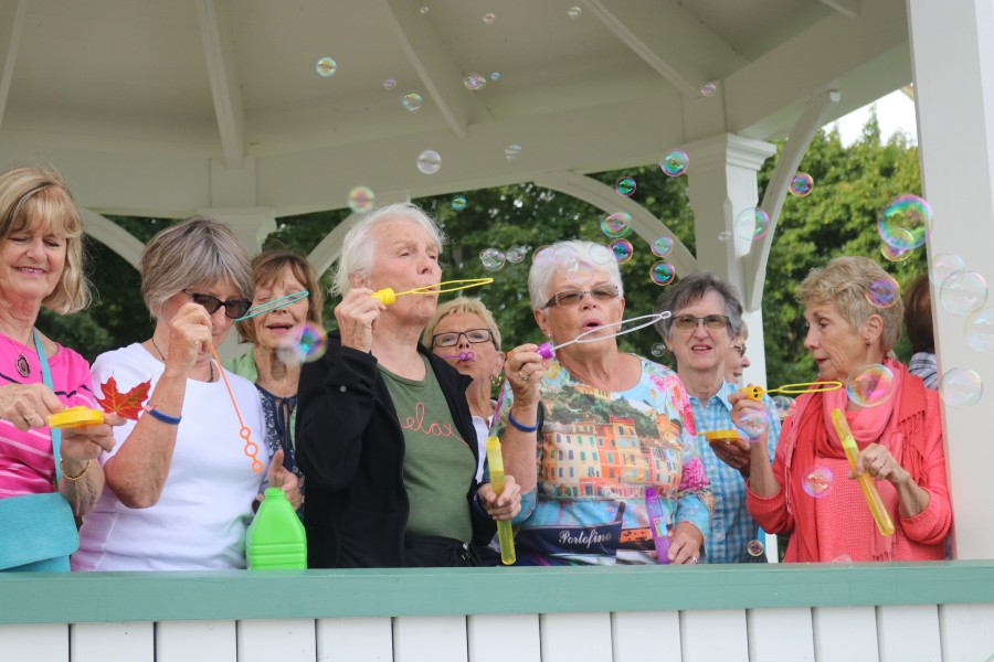 Members of a local walking group blow bubbles in support of people with pulmonary fibrosis. (Dariya Baiguzhiyeva/Niagara Now)