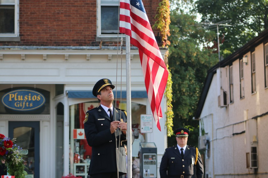 Chief of Niagara Emergency Medical Services Kevin Smith lowers the flag.(Dariya Baiguzhiyeva/Niagara Now)